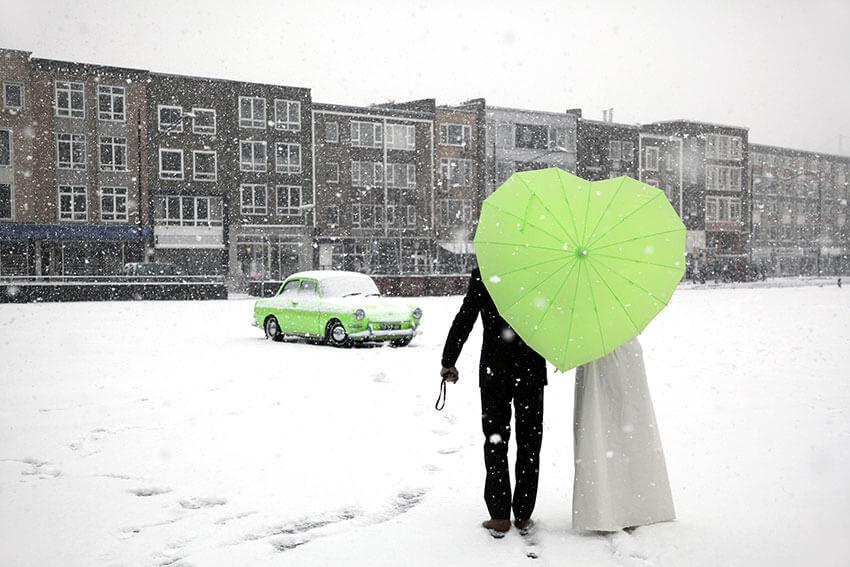 Bruidspaar in de sneeuw met groene auto